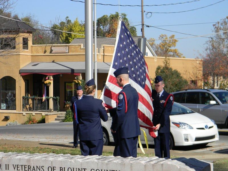 Three servicemembers salute the American flag as it is raised on the pole